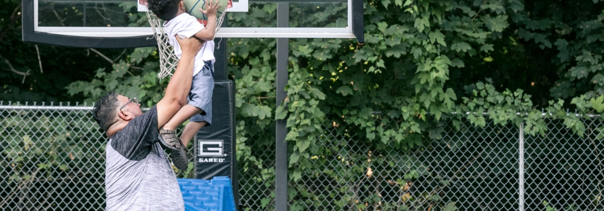 Father lifting up son to dunk a basketball