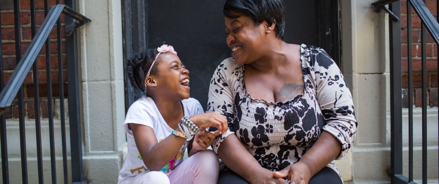 Woman and little girl laughing together on doorstep